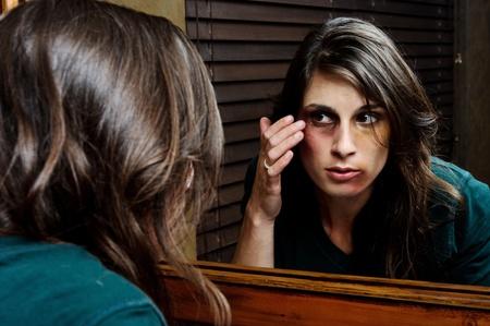 mujer golpeada: Mujer maltratada comprueba el alcance de sus heridas en el espejo del ba�o Foto de archivo