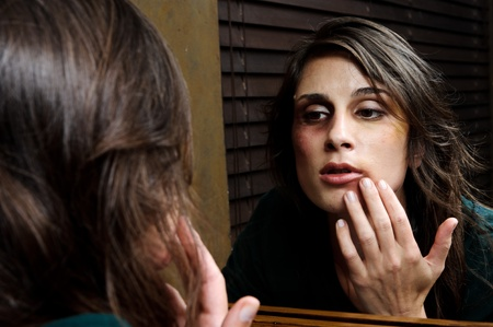 Battered woman checks the extent of her injuries in the bathroom mirror Stock Photo - 8726458