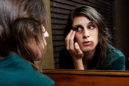 Battered woman checks the extent of her injuries in the bathroom mirror photo