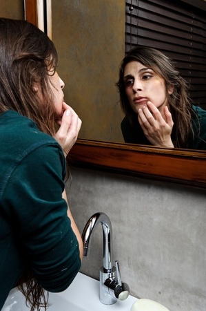 battered woman: Battered woman checks the extent of her injuries in the bathroom mirror