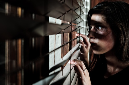 blinds: Fearful battered woman peeking through the blinds to see if her husband is home