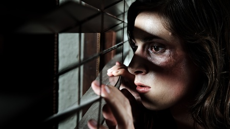 Fearful battered woman peeking through the blinds to see if her husband is home photo