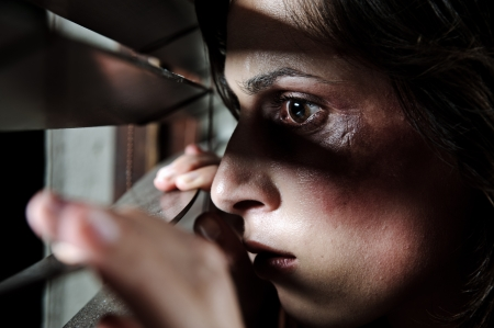 beaten woman: Fearful battered woman peeking through the blinds to see if her husband is home