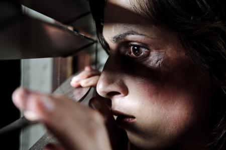 abuso: Mujer maltratada temerosa leerlo a trav�s de las persianas para ver si su marido es hogar Foto de archivo