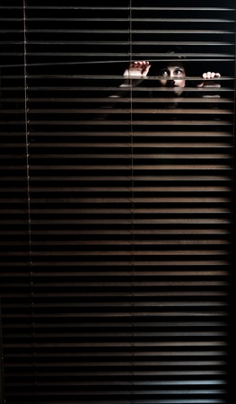 Mysteus woman pulls the blinds apart to see the outside world  Stock Photo - 8726442