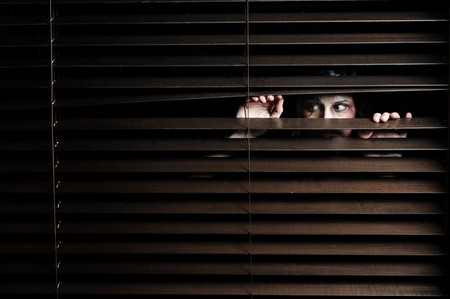 Mysterious woman pulls the blinds apart to see the outside world Stock Photo - 8726450