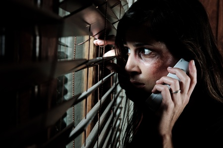 battered woman: Fearful battered woman peeking through the blinds to see if her husband is home while calling for help Stock Photo
