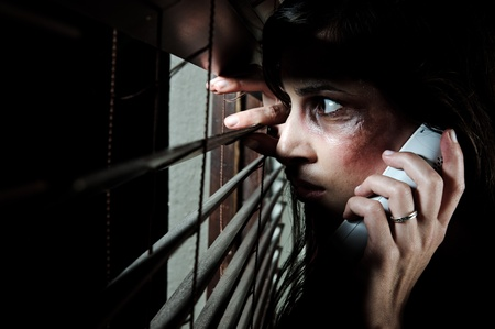 Fearful battered woman peeking through the blinds to see if her husband is home while calling for help photo
