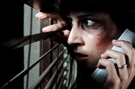 fearful: Fearful battered woman peeking through the blinds to see if her husband is home while calling for help Stock Photo