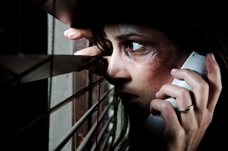 beaten woman: Fearful battered woman peeking through the blinds to see if her husband is home while calling for help Stock Photo