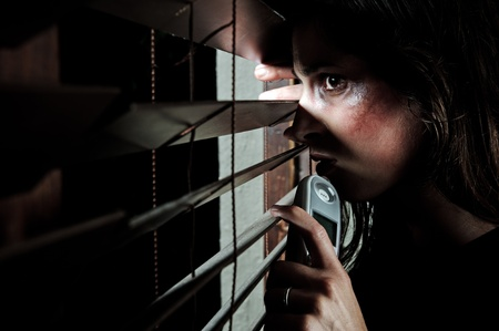 fearful: Fearful battered woman peeking through the blinds to see if her husband is home. she is contemplating whether to call the domestic violence hotline Stock Photo