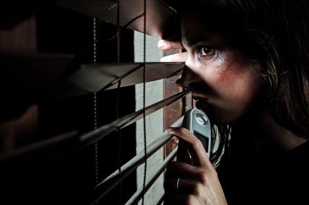 mujer golpeada: Mujer maltratada temerosa leerlo a trav�s de las persianas para ver si su marido es hogar. ella est� contemplando si se va a llamar a la l�nea directa de violencia dom�stica Foto de archivo