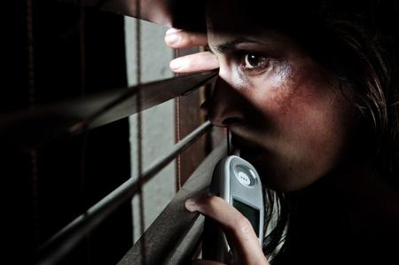 mujer golpeada: Temeroso de mujer maltratada leerlo a trav�s de las persianas para ver si su esposo es hogar. ella est� contemplando si se va a llamar a la l�nea directa de la violencia en el hogar