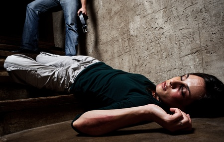 injure: Battered woman lies lifelessly at the bottom of stairs with a faceless man holding a belt, a conceptual shoot portraying the process and effects of domestic violence  Stock Photo