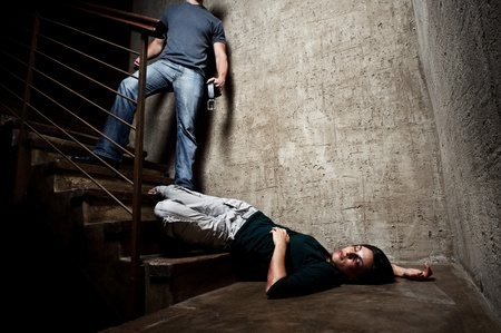 victim: Battered woman lies lifelessly at the bottom of stairs with a faceless man holding a belt, a conceptual shoot portraying the process and effects of domestic violence  Stock Photo