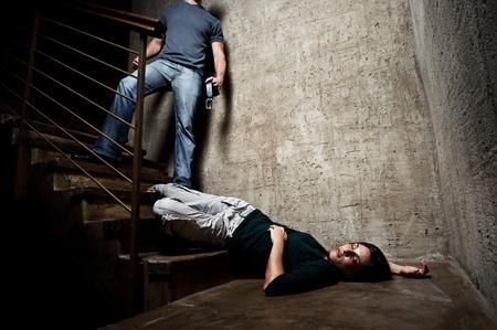 violencia intrafamiliar: Mujer maltratada se encuentra lifelessly en la parte inferior de las escaleras con un hombre sin rostro que se sostiene un cintur�n, un rodaje conceptual, representando el proceso y los efectos de la violencia dom�stica