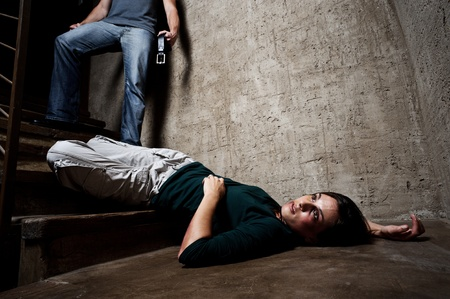 horrified: Battered woman lies lifelessly at the bottom of stairs with a faceless man holding a belt, a conceptual shoot portraying the process and effects of domestic violence  Stock Photo