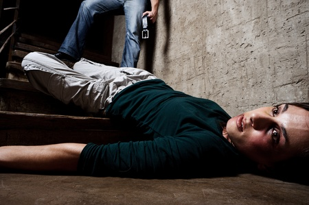 fainted: Battered woman lies lifelessly at the bottom of stairs with a faceless man holding a belt, a conceptual shoot portraying the process and effects of domestic violence  Stock Photo