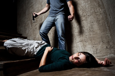 murder: Battered woman lies lifelessly at the bottom of stairs with a faceless man holding a belt, a conceptual shoot portraying the process and effects of domestic violence  Stock Photo