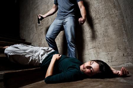 violencia: Mujer maltratada se encuentra lifelessly en la parte inferior de las escaleras con un hombre sin rostro que se sostiene un cintur�n, un rodaje conceptual, representando el proceso y los efectos de la violencia dom�stica
