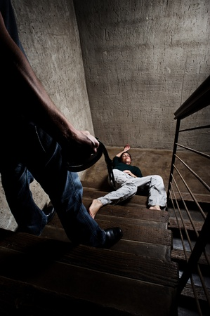 fainted: Battered woman lies lifelessly at the bottom of stairs, a conceptual shoot depicting the effects of domestic violence  Stock Photo