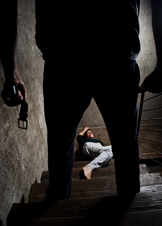 battered woman: Battered woman lies lifelessly at the bottom of stairs with a faceless man holding a belt, a conceptual shoot portraying the process and effects of domestic violence  Stock Photo