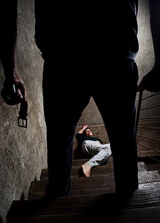 mujer golpeada: Mujer maltratada se encuentra lifelessly en la parte inferior de las escaleras con un hombre sin rostro que se sostiene un cintur�n, un rodaje conceptual, representando el proceso y los efectos de la violencia dom�stica