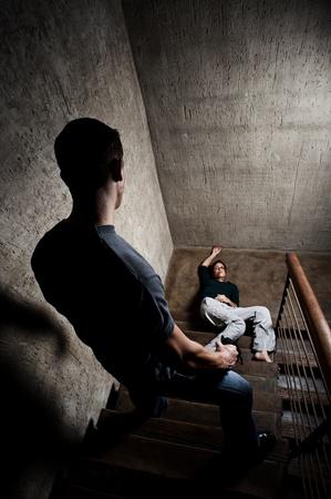violencia intrafamiliar: Mujer maltratada se encuentra lifelessly en la parte inferior de las escaleras, un rodaje conceptual que representan los efectos de la violencia dom�stica