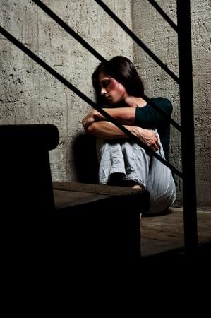 mujer golpeada: Abusado de la mujer en la esquina de una escalera reconfortante a s� misma  Foto de archivo