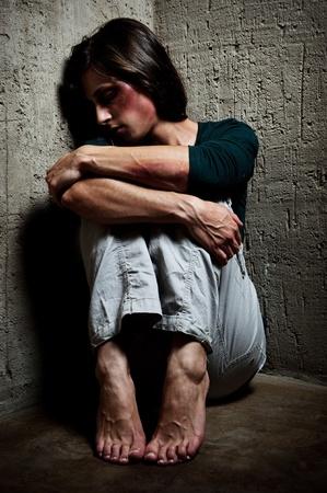 abuso: Abusado de la mujer en la esquina de una escalera reconfortante a s� misma  Foto de archivo