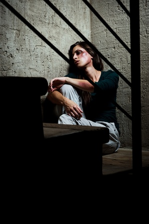 traumatised: Abused woman in the corner of a stairway comforting herself  Stock Photo