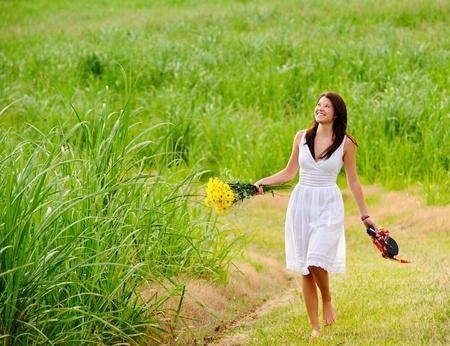 Adorable girl walks barefoot in field with flowers in hand photo