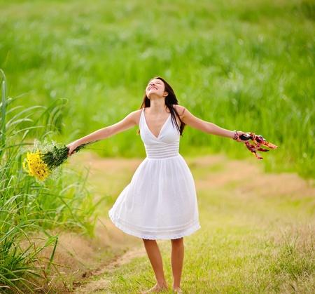 행복한 여자는 자유롭고 봄의 햇빛을 즐깁니다.