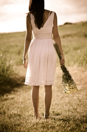 old style image of girl standing outdoors with flowers in hand photo