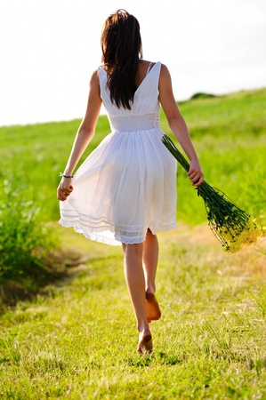 White dress skipping girl in field with flowers at sunset