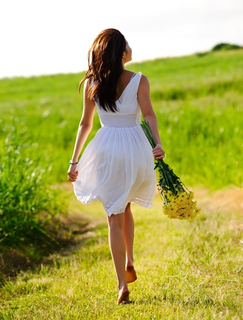 White dress skipping girl in field with flowers at sunset Stock Photo - 8726309