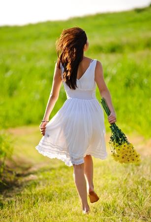 Weißes Kleid überspringen Mädchen im Feld mit Blumen bei Sonnenuntergang