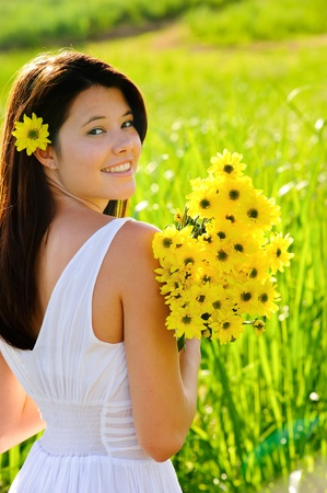 Adorable girl with flowers poses in a field during summer afternoon. Stock Photo - 8726282