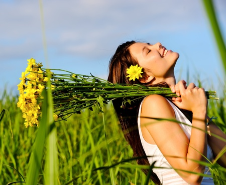 candid adorable girl in white dress is carefree with flowers in green field during spring.  Stock Photo - 8726299