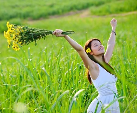 back of woman: Carefree chica adorable con armas en campo. concepto de andjoy de libertad de verano.