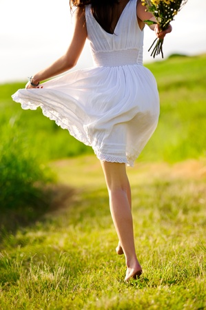 White dress skipping girl in field with flowers at sunset Stock Photo - 8726277