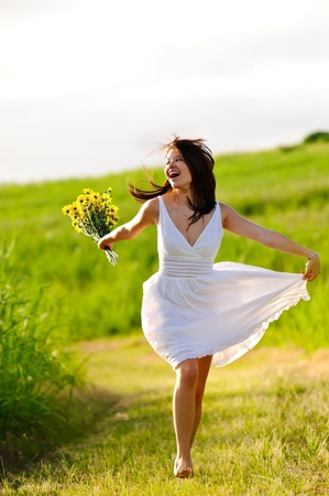 Candid skipping carefree adorable woman in field with flowers at summer sunset. photo
