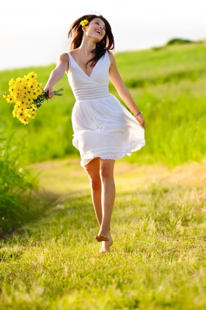 yellow dress: Candid skipping carefree adorable woman in field with flowers at summer sunset.