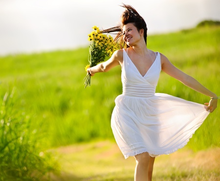 Candid skipping carefree adorable woman in field with flowers at summer sunset. Stock Photo - 8726322