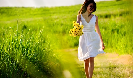 Candid skipping carefree adorable woman in field with flowers at summer sunset. Stock Photo - 8726308