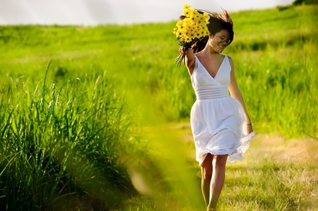 healthy person: Candid skipping carefree adorable woman in field with flowers at summer sunset.