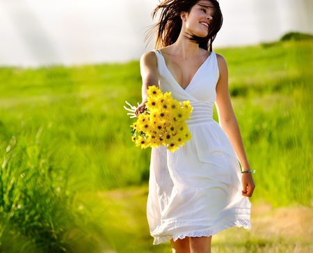 Candid skipping carefree adorable woman in field with flowers at summer sunset. Stock Photo - 8726331