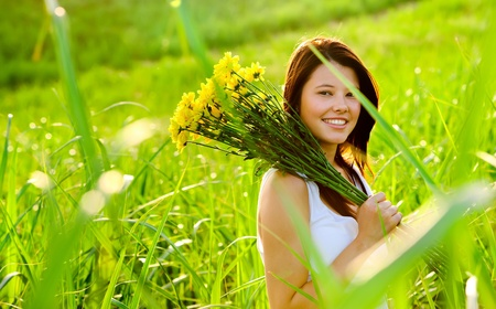 Adorable girl with flowers poses in a field during summer afternoon.  photo