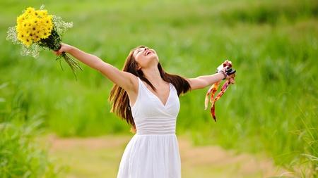 Zorgeloos meisje is gelukkig in veld met bloemen
