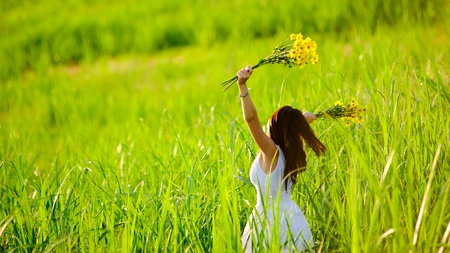 yellow dress: woman in white dress triwls in field with flowers in hand. summer carefree girl